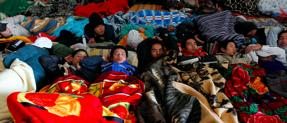 Vietnamese refugees rest in a shed while awaiting transportation at the Libyan and Tunisian border crossing of Ras Jdir after fleeing unrest in Libya February 27, 2011. People in Tunisia and Egypt are driving to the border to help those arriving from Libya, with many hosting strangers in their homes, international aid groups said on Friday. More than 30,000 people have streamed across land borders in response to violence in Libya, mainly Tunisians and Egyptians who had been working in the North African country, according to the International Organisation for Migration. REUTERS/Zohra Bensemra