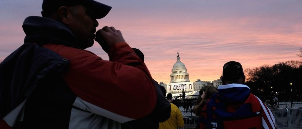 A Trump supporter takes a drag of a cigarette as the sun begins to rise over the U.S. Capitol on the National Mall before U.S. President-elect Donald Trump is to be sworn in in Washington