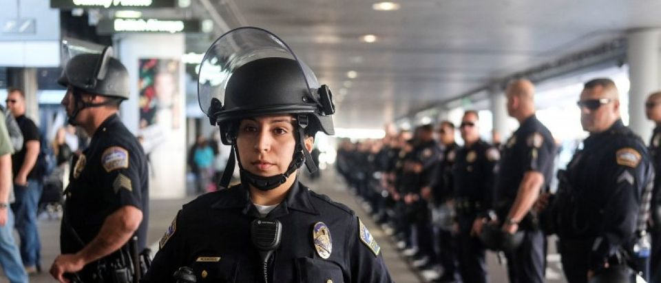 Police officers stand guard as demonstrators in support of and against the immigration rules implemented by U.S. President Donald Trump's administration, rally at Los Angeles international airport in Los Angeles