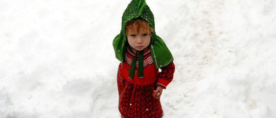 An Internally displaced Afghan child stands outside her shelter during a snowfall in Kabul, Afghanistan