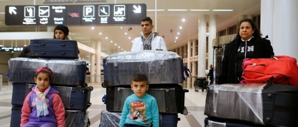 The al-Qassab family, Iraqi Christian refugees from Mosul, pose with their luggage at Beirut international airport ahead of their travel to the United States