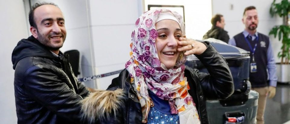 Syrian refugees Baraa and her husband Abdulmajeed Haj Khalaf smile after arriving at O'Hare International Airport in Chicago