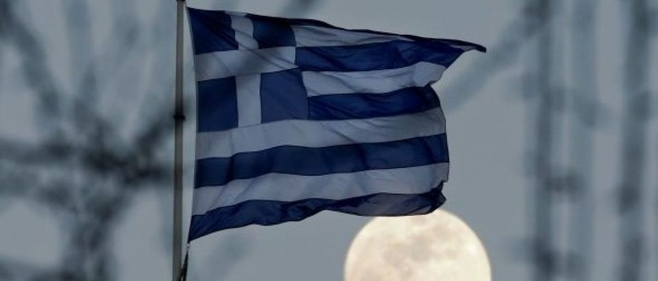 A Greek national flag flutters as the moon rises in Athens