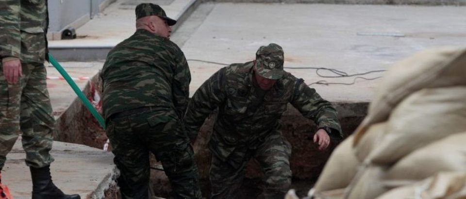 Military officers jump into a hole in the ground to inspect a 250 kg World War Two bomb that was found during excavation works at a gas station on the northern city of Thessaloniki