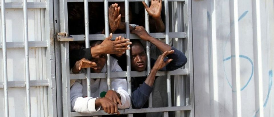 FILE PHOTO: Illegal migrants, who have been detained after trying to get to Europe, look out of barred door of a detention hut at a detention camp in Gheryan, outside Tripoli