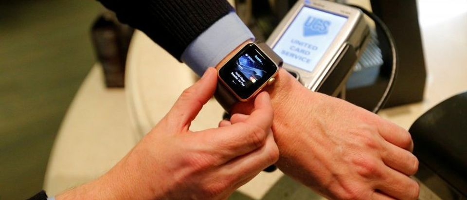 FILE PHOTO: A man uses an Apple Watch to demonstrate the mobile payment service Apple Pay at a cafe, October 3, 2016. Picture taken October 3, 2016. REUTERS/Maxim Zmeyev/File Photo