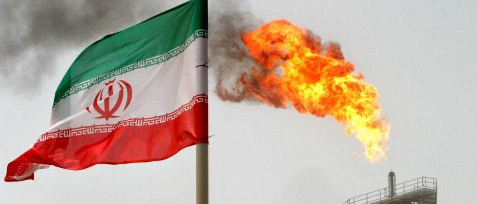 FILE PHOTO - A gas flare on an oil production platform in the Soroush oil fields is seen alongside an Iranian flag in the Persian Gulf