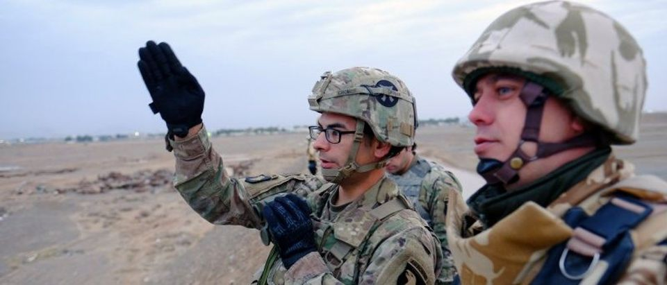 Romanian and American military advisers locate a target in preparation for a live-fire artillery exercise with Afghan troops outside Kandahar Air Field