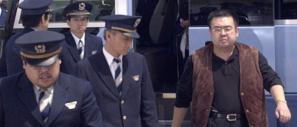 A man believed to be North Korean heir-apparent Kim Jong Nam is escorted by police as he boards a plane upon his deportation from Japan at Tokyo's Narita international airport in Narita, Japan