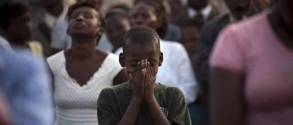 A boy prays at the Festival of Hope at a soccer stadium in downtown Port-au-Prince
