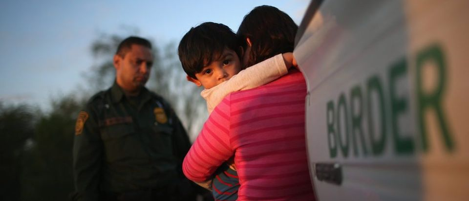 A one-year-old from El Salvador clings to his mother after she turned themselves in to Border Patrol agents on December 7, 2015 near Rio Grande City, Texas. (John Moore/Getty Images)