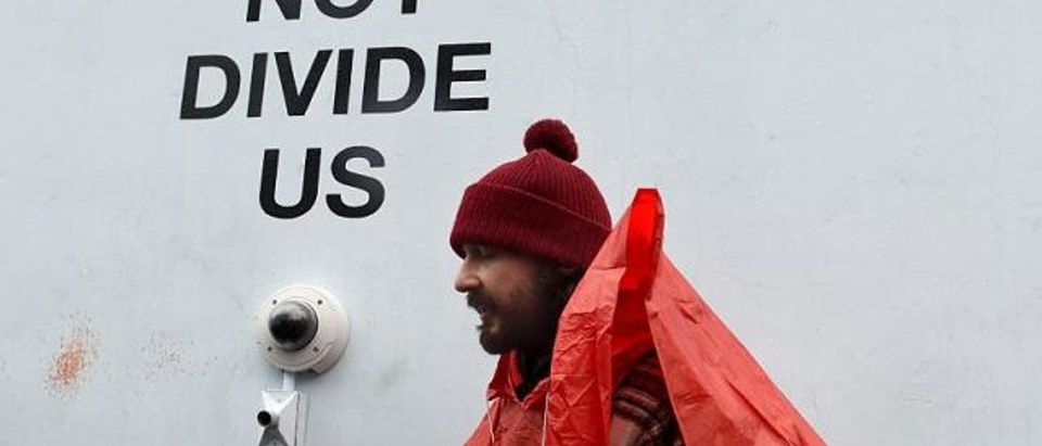 Shia LaBeouf is seen near the camera during his He Will Not Divide Us livestream outside the Museum of the Moving Image in Astoria, in the Queens borough of New York January 24, 2017 as a protest against President Donald Trump. LaBeouf has installed a camera at the Museum of the Moving Image in New York that will run a continuous live stream for the duration of Trump's presidency. LaBeouf is inviting the public to participate in the project by saying the phrase, He will not divide us, into the camera. (Photo credit: TIMOTHY A. CLARY/AFP/Getty Images)