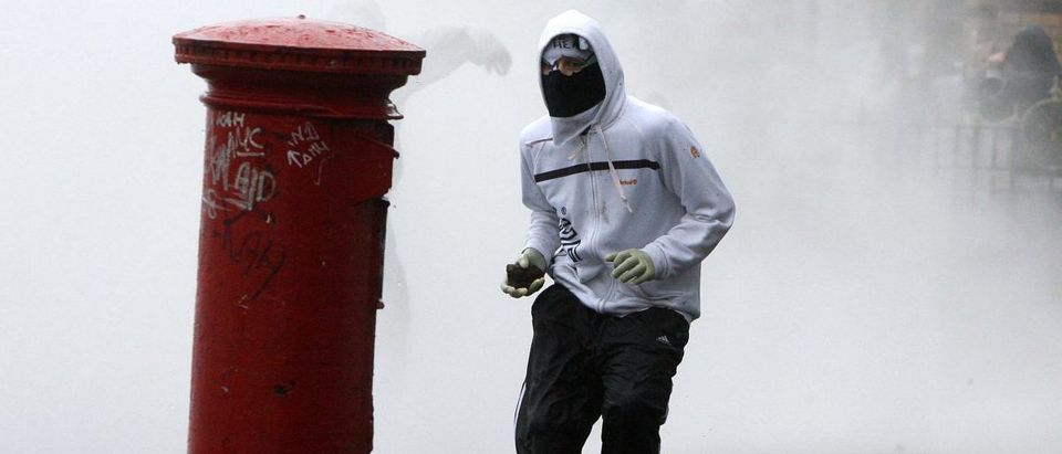 A masked youth prepares to throw a stone at police officers in the Ardoyne area of North Belfast