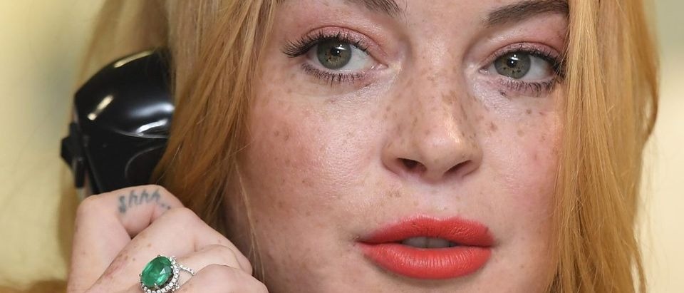 U.S. actress Lindsay Lohan speaks on a telephone as dealers work on a trading floor during a charity day at BGC Partners in the Canary Wharf business district in London, Britain September 12, 2016. REUTERS/Toby Melville