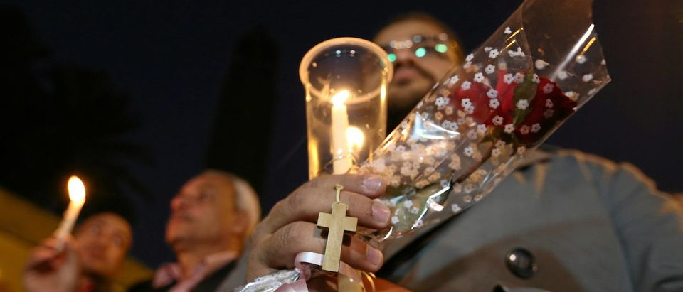 Egyptians hold candles and a cross in front of the Coptic Christian Cathedral in tribute to the victims of the bomb attack, following a deadly explosion inside a Coptic cathedral in Cairo, Egypt December 17, 2016. REUTERS/Mohamed Abd El Ghany