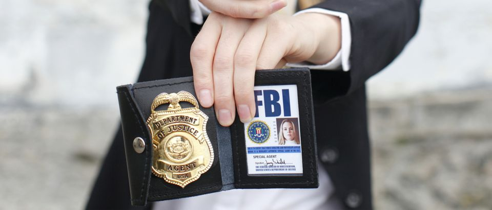 FBI agent holds a badge (Shutterstock/Peter Kim)