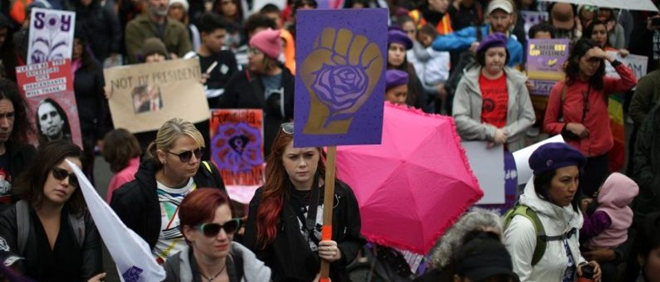 People listen to speakers in the rain at a rally for International Women's Day in Los Angeles