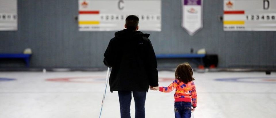 "A father and daughter, who are refugees from Syria, walk the ice as they were introduced to the sport of curling at the Royal Canadian Curling Club during an event put on by the ""Together Project"", in Toronto"