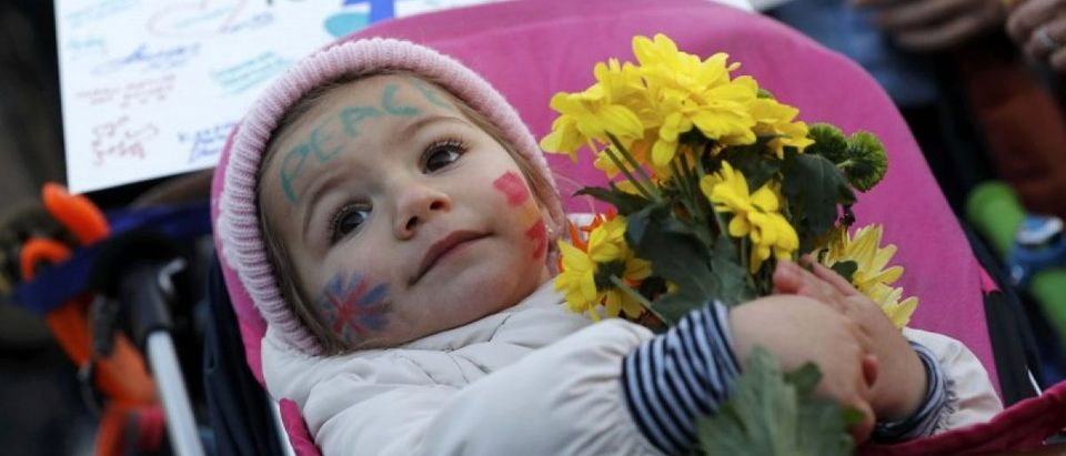 A baby holds a bunch of flowers at a vigil in Trafalgar Square the day after an attack, in London, Britain March 23, 2017. REUTERS/Darren Staples
