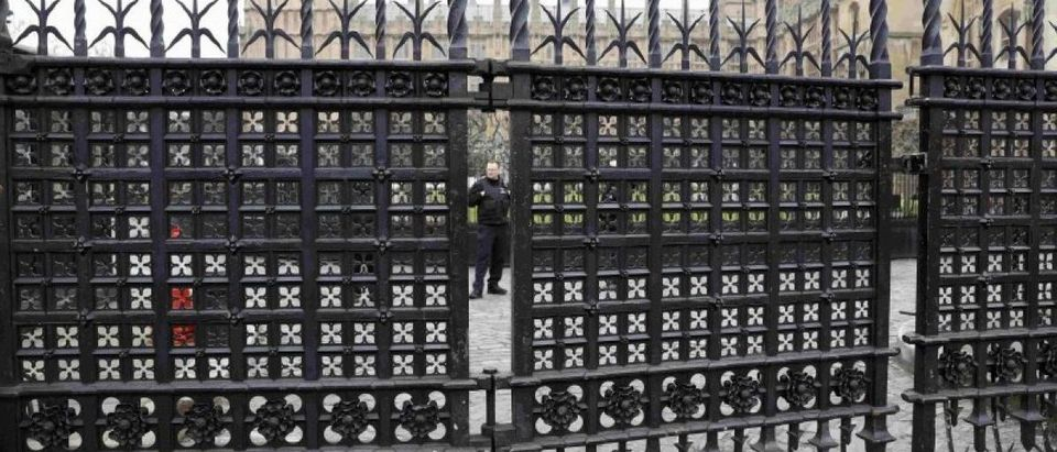 A police officer stands behind Carriage Gates at the Houses of Parliament, following a recent attack in Westminster, London