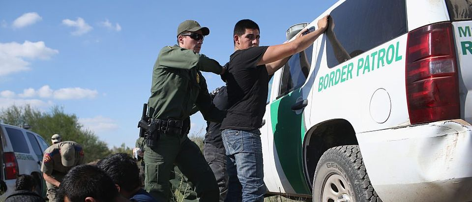 A U.S. Border Patrol officer body searches an undocumented immigrant after he illegally crossed the U.S.-Mexico border and was caught on December 7, 2015 near Rio Grande City, Texas. (Photo by John Moore/Getty Images)