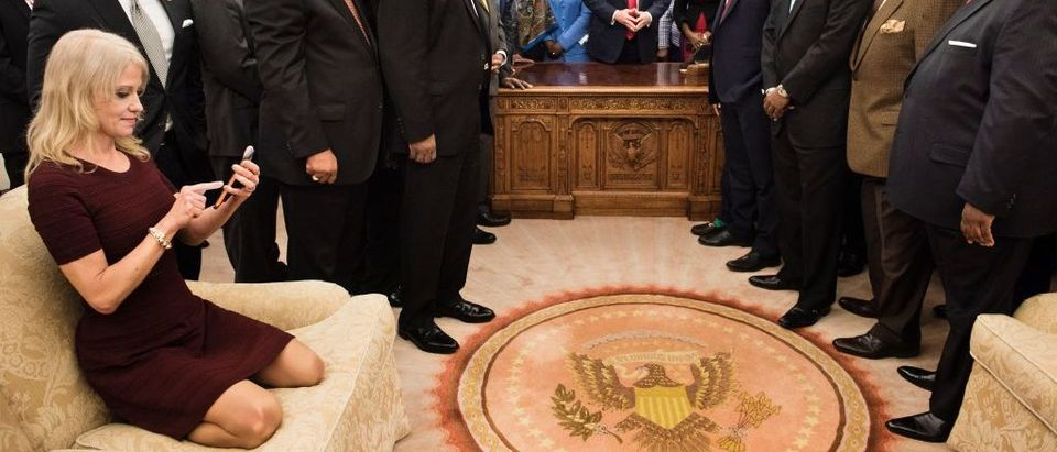 TOPSHOT - Counselor to the President Kellyanne Conway (L) checks her phone after taking a photo as US President Donald Trump and leaders of historically black universities and colleges pose for a group photo in the Oval Office of the White House before a meeting with US Vice President Mike Pence February 27, 2017 in Washington, DC. BRENDAN SMIALOWSKI/AFP/Getty Images