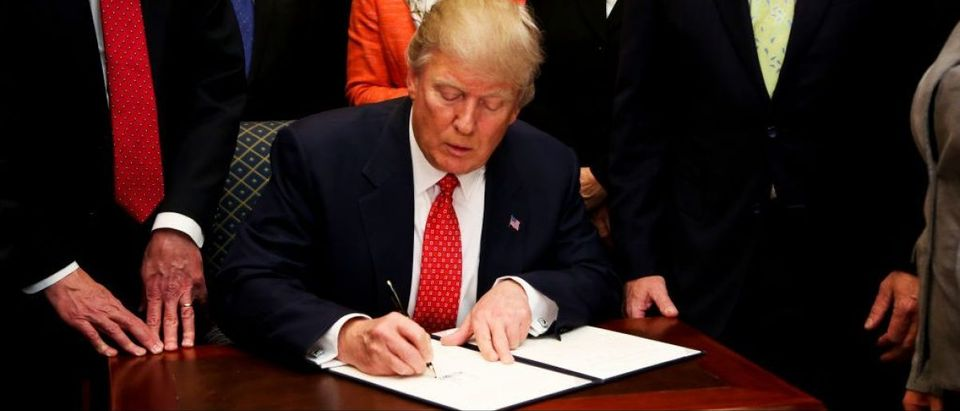 WASHINGTON, D.C. - FEBRUARY 28: President Donald Trump signs an Executive Order to begin the roll-back of environmental regulations put in place by the Obama administration February 28, 2017 in the Roosevelt Room of the White House in Washington, D.C. The Clean Water Rule, also known as WOTUS, the Waters of the U.S. rule, has been unpopular with some farmers, housing developers and energy companies. (Photo by Aude Guerrucci-Pool/Getty Images)