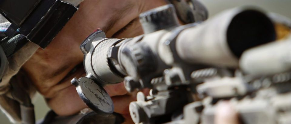 Sergeant Chase Campbell of Delta Company, a part of Task Force 1-66 scans the area through the scope of his sniper rifle watching over Arghandab River in Kandahar province, September 8, 2010. REUTERS/Oleg Popov