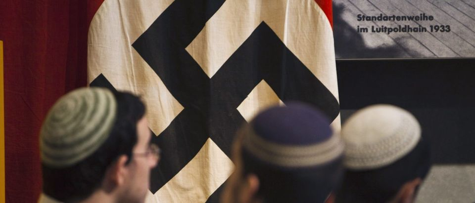 Visitors stand in front of a flag with the Nazi swastika at Yad Vashem's Holocaust History Museum in Jerusalem April 18, 2012. Starting Wednesday evening, Israel marks the annual memorial day commemorating the six million Jews killed by the Nazis in the Holocaust during World War Two. REUTERS/Nir Elias