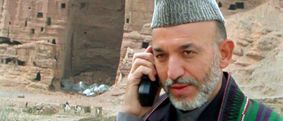 HAMID KARZAI SPEAKS ON THE SATELLITE PHONE IN BAMIYAN.