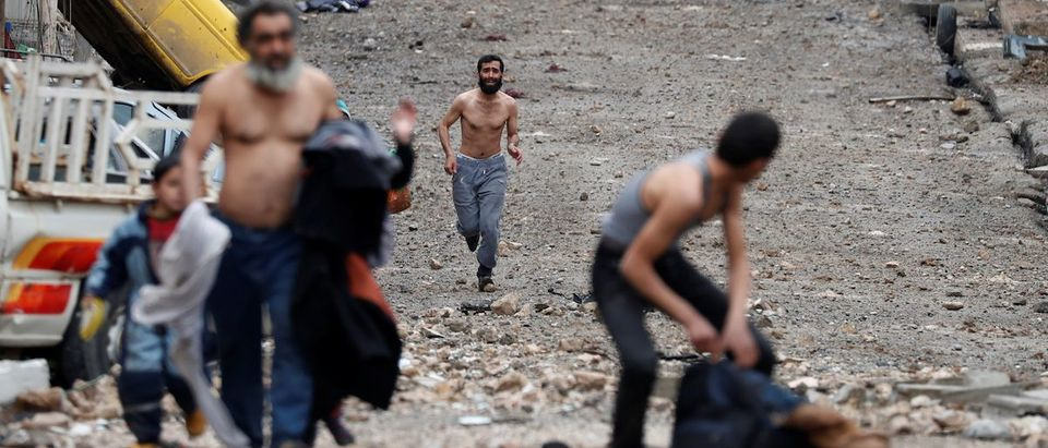 A man runs from Islamic State controlled part of Mosul towards Iraqi special forces soldiers during a battle in Mosul