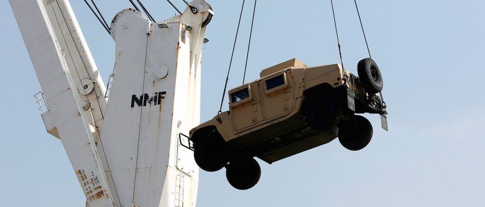 Workers unload a Humvee, part of a military donation from the U.S. government to the Lebanese army, during a ceremony at Beirut's port