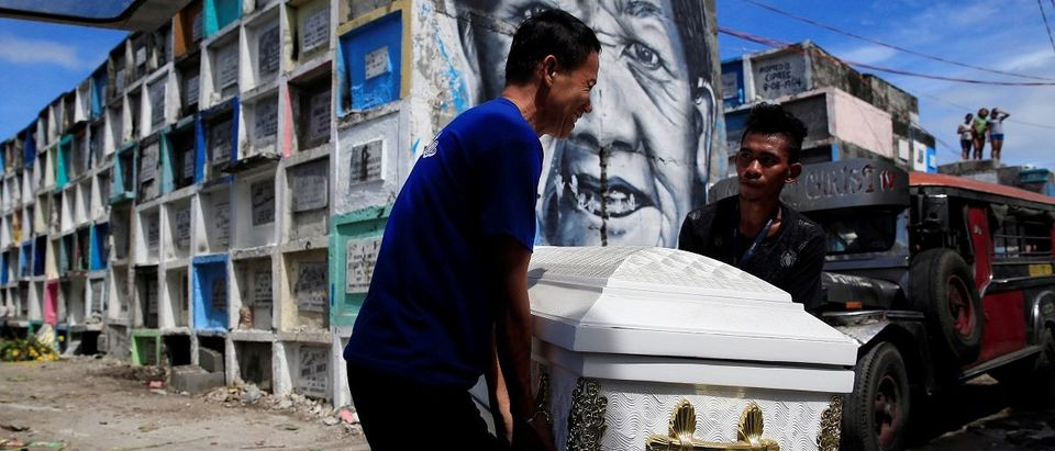 Graveyard workers carry the coffin of Eddie Languido, 56, victim of a summary execution by unknown assailants related to the drug war, during his funeral at the Navotas cemetery, north of Metro Manila