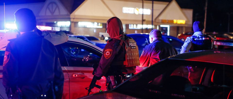 Police officers draw their weapons during a protest in Ferguson