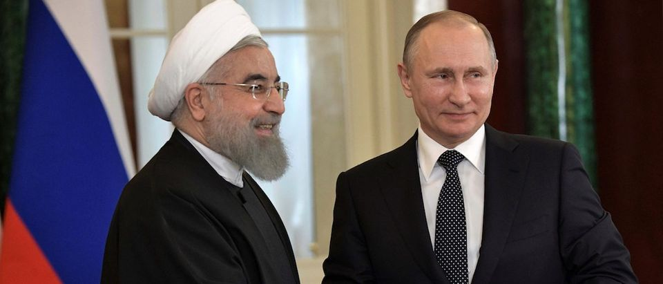 Russian President Putin shakes hands with Iranian President Rouhani during joint news conference following their meeting at Kremlin in Moscow