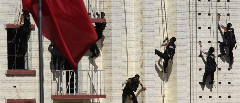 Armed policemen from the SWAT Unit climb up a building during an anti-terrorism drill in Beijing
