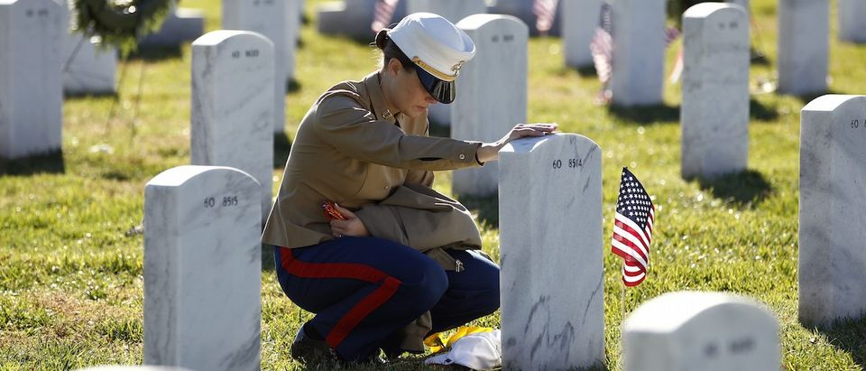 Marine kneels at the grave of fellow soldier at Arlington National Cemetery in Virginia