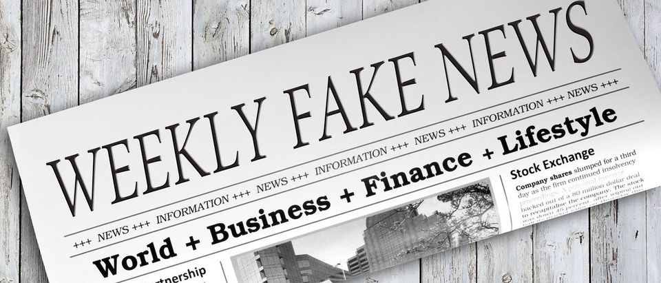Weekly Fake News Newspaper on grey wooden background (Shutterstock/docstockmedia)