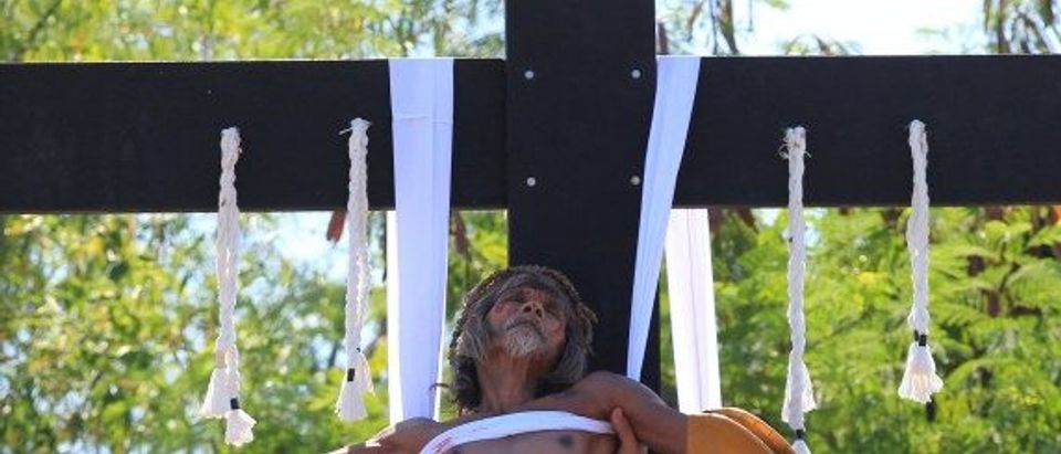 Willy Salvador, who is portraying Jesus Christ, is lowered after he was nailed to a wooden cross during a Good Friday crucifixion re-enactment in San Juan village, Pampanga province, north of Manila