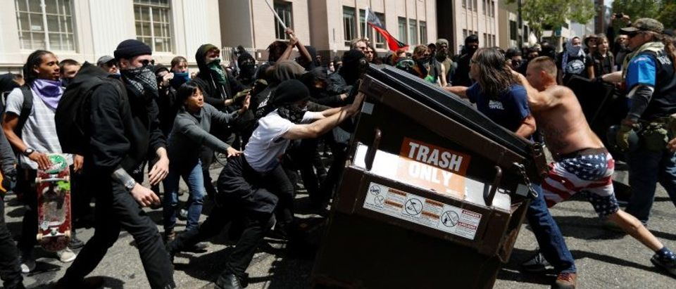 Demonstrators for (R) and against (L) U.S. President Donald Trump push a garbage container toward each other during a rally in Berkeley