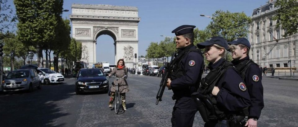 Armed French police patrol the Champs Elysees Avenue the day after a policeman was killed and two others were wounded in a shooting incident in Paris