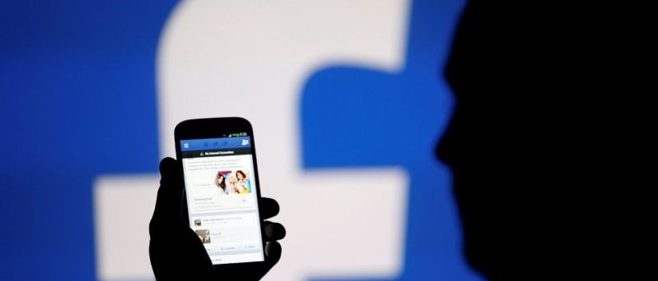 FILE PHOTO: A man is silhouetted against a video screen with a Facebook logo as he poses with a smartphone in this photo illustration