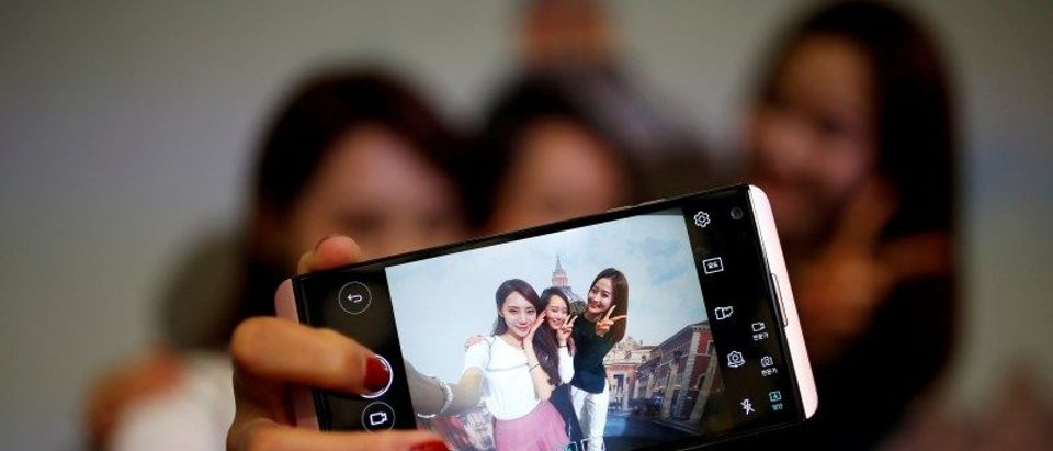 FILE PHOTO: Models pose for photographs with a LG electronics' new V20 premium smartphone during its unveiling ceremony in Seoul
