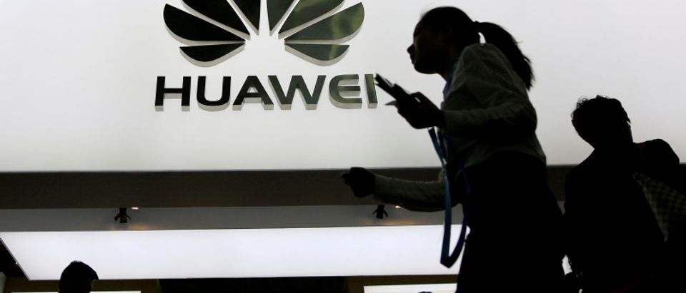 FILE PHOTO: People walk past a sign board of Huawei at CES Asia 2016 in Shanghai
