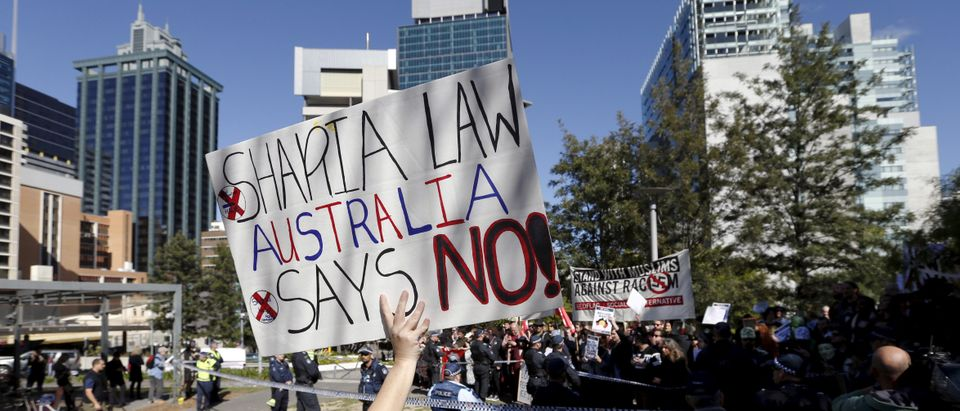 A woman holds up a banner against Sharia law in Australia as she faces another rally calling for an end to racism in Brisbane
