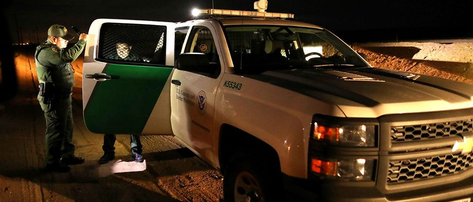 U.S. border patrol agents detain a man after he was spotted crossing illegally into the United States along the Mexican border near Calexico, California