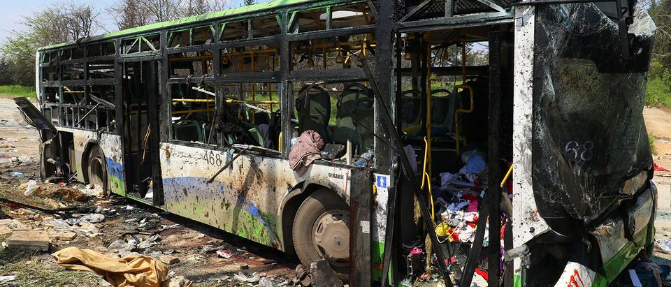 A damaged bus is seen after an explosion yesterday at insurgent-held al-Rashideen