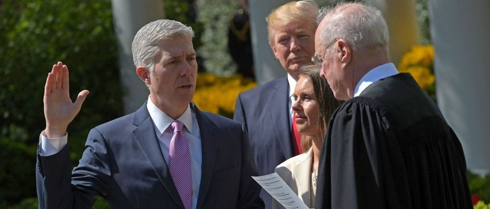 President Donald Trump watches as Justice Anthony Kennedy administers the oath of office to Neil Gorsuch as an associate justice of the US Supreme Court in the Rose Garden of the White House on April 10, 2017 in Washington, D.C. (Photo credit: MANDEL NGAN/AFP/Getty Images)
