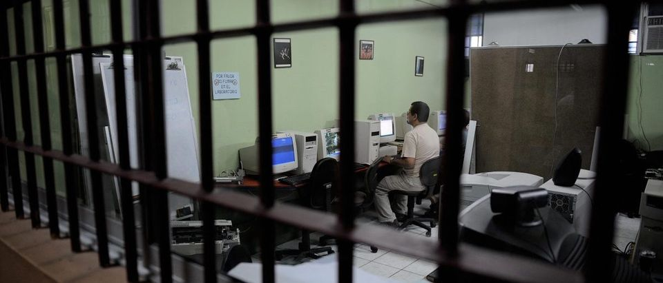 A prisoner works in a computer at the la