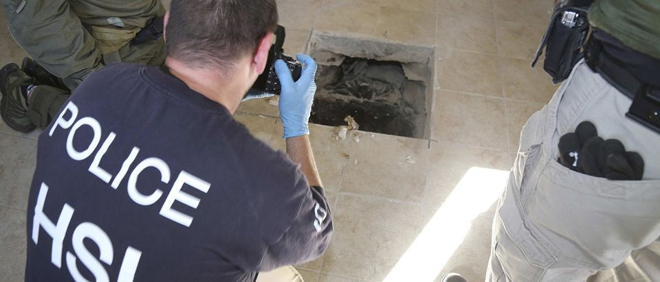 A U.S. HSI Special Response Team agent photographs the tunnel exit point in Calexico California